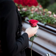 Person next to dark wooden casket, wearing black suit, holding red rose