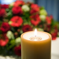 Lit beige candle, with bouquet of red flowers blurred in background